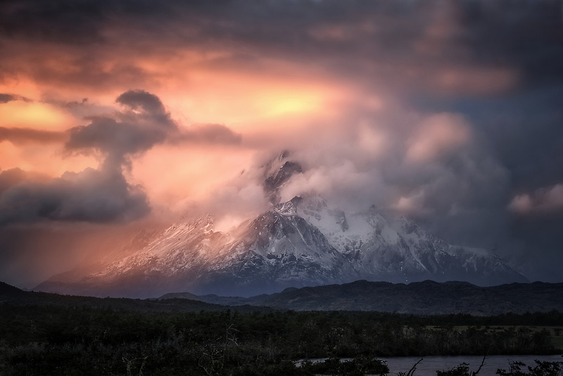 Cotton candy clouds swirling around Paine Mountain. Torres Del Paine National Park, Chile