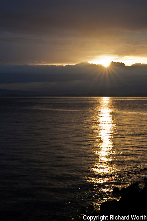 The morning sun's rays find their way through the clouds on the eastern shores of San Francisco Bay.