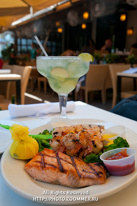 Seafood plate with fish and large Mojito cocktail on Ocean Drive Miami Beach