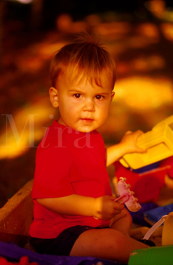 Portrait of a toddler boy at play with toys in a sandbox amidst dappled light and shade. Sam. Georgia.