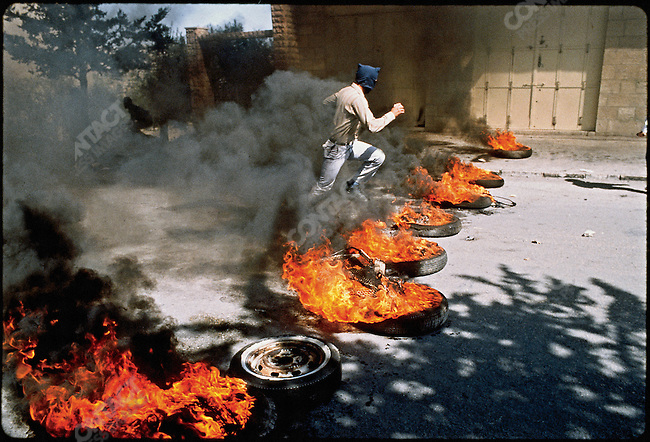 A Palestinian protester flees as Israeli troops fire shots in his direction. Bethlehem, West Bank. March 1988