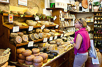 Shopper in Italian artisan cheese shop, Del Bottega Naturista selling Pecorino Stagionato aged cheese in Pienza, Tuscany, Italy