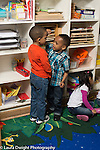Preschool 4 year olds two boys comparing height shorter boy with his hand on taller boy's forehead, talking