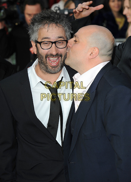 "DAVID BADDIEL & OMID DJALILI.The World Premiere of ""The Infidel"", Hammersmith Apollo, London, England..8th April 2010.half length suit jacket smiling laughing  black white shirt beard facial hair kissing kiss cheek funny profile glasses mouth open.CAP/BEL.©Tom Belcher/Capital Pictures."