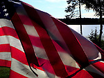 A tattered American Flag flies proudly over Spider Lake at sunset.