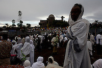 a pilgrim waits for an orthodox priest to baptize her during the Saint john the baptist orthodox religious festival in Shankora, Ethiopia on Thursday July 06 2006.Tens of thousands of believers gather for the holy festival which is famous throughout the country for the holiness of its water. Many believe that the holy water of a nearby waterfall if drank during the festival can cure any disease, especially HIV AIDS. Preachers come from all over the country to try to persuade the ill not to take conventional medication, not to go to hospitals, but only to drink holy water and pray. the clash between traditional believes and modern medicine is a serious issue in Ethiopia.
