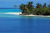 Idyllic palm lined white sand beach surrounded by blue tropical waters, Maldives.