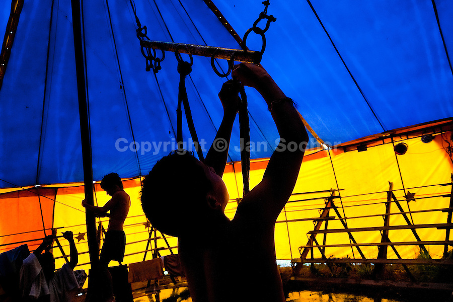 Raimundo, a nine-year old Colombian boy, prepares a flying trapeze at the Circo Anny, a family run circus wandering the Amazon region of Ecuador, 4 July 2010. The Circo Anny circus belongs to the old-fashioned traveling circuses with a usual mixture of acrobat, clown and comic acts. Due to the general loss of popularity caused by modern forms of entertainment such as movies, TV shows or internet, these small family enterprises balance on the edge of survival. Circuses were pushed away and now they have to set up their shows in more remote villages. The circus art and culture is slowly dying.