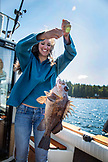 USA, Alaska, Ketchikan, a female fisherman shows off her catch while fishing the Behm Canal near Clarence Straight, Knudsen Cove along the Tongass Narrows