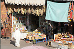 A man walks by a rug and spice vendor in the Souk in Marrakesh, Morocco.