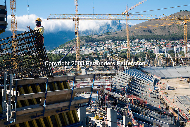CAPE TOWN, SOUTH AFRICA - FEBRUARY 18: Piet Skosana (c), age 48, and construction worker, stands on the top of the newly built Green Point stadium on February 18, 2008 in Cape Town, South Africa. About 1500 workers construct the new stadium that is built for the World Cup Soccer tournament held in South Africa in June 2010. The stadium will have a retractable roof and a capacity of 68 000. (Photo by: Per-Anders Pettersson Reportage by Getty Images)..