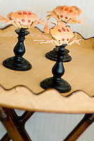 Painted crab shells on candle holders used as decorative objects
