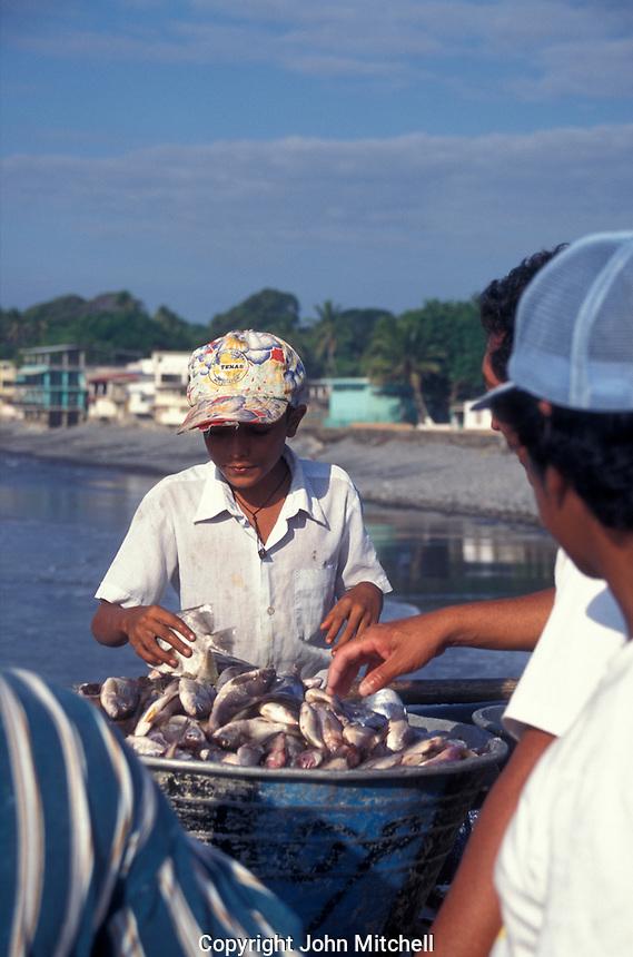 Boy selling fresh fish on the town pier in La Libertad, El Salvador