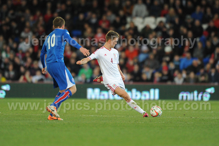 Emyr Huws of Wales clears the ball before he is tackled by Gylfi Thor Sigurosson of Iceland and Spurs. Cardiff City Stadium, Cardiff, Wales, Wednesday 5th March 2014. The Football Association of Wales - Vauxhall International Friendly - Wales v Iceland. Pictures by Jeff Thomas Photography - www.jaypics.photoshelter.com - Contact: thomastwotimes@live.co.uk - 07837 386244