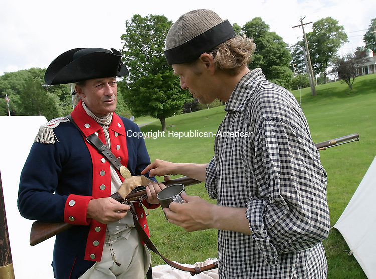 MIDDLEBURY, CT, 27 June 2006- 062706BZ02- Mike Fitzgerald, of Pittsburgh, PA, an &quot;American officer&quot;, left, and Dave Fagerberg, of Prairie Village, Kansas, an &quot;American soldier&quot;, look at Fagerberg's short land pattern musket, known as a 2nd model Brown Bess, after setting up camp in a field near the Shepardson Community Center in Middlebury Tuesday afternoon.  They are part of a group walking the route General Rochambeau took from Newport, RI, to Yorktown, VA.<br /> Jamison C. Bazinet Republican-American