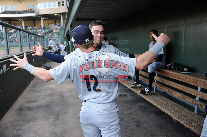 Infielder Dante Bichette Jr. (19) of the Charleston RiverDogs, rear, chest bumps catcher Nick McCoy (12) in the dugout just before a game against the Greenville Drive on May 31, 2012, at Fluor Field at the West End in Greenville, South Carolina. Charleston won, 13-2.  (Tom Priddy/Four Seam Images)