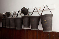 Leather fire buckets lining the corridor are painted with an L for Longford below an Earl's coronet