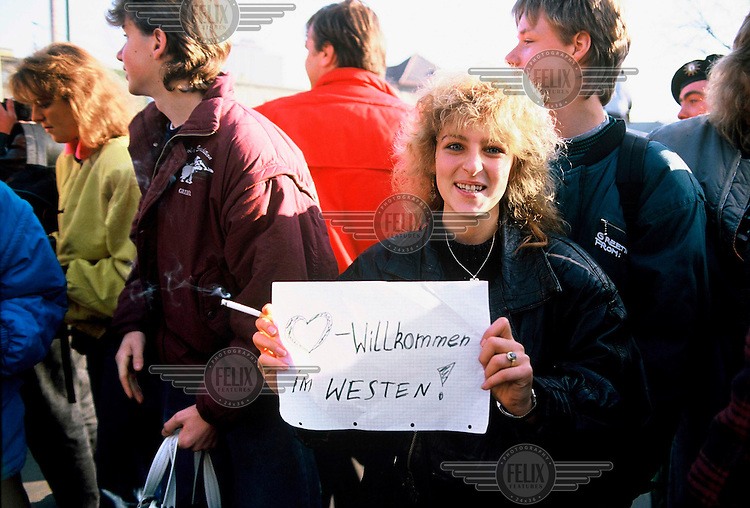 A woman holds a sign reading 'Welcome to the West' as East Germans enter West Berlin after the opening of the Berlin Wall.