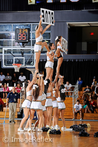 "1 December 2012:  FIU's cheerleaders form a tower and hold up signs, unaware that the sign with the word ""BLUE"" is upside-down in the second half as the University of South Alabama Jaguars defeated the FIU Golden Panthers, 79-68, at the U.S. Century Bank Arena in Miami, Florida."