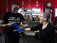 NWA Democrat-Gazette/CHARLIE KAIJO Strightright boxing coach Bernard Oliver puts hand wraps on the hands of Jonelle Lipscomb (from left) during a boxing class geared towards people with Parkinson's disease, Monday, December 10, 2018 at Straightright Boxing and Fitness Springdale.