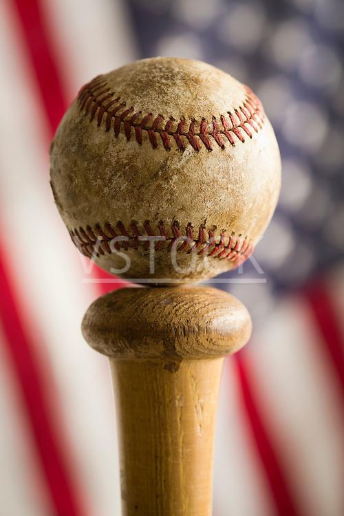 Baseball on top of bat against American flag
