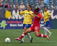 Brazilian defender Daiane (4) and Canadian midfielder Desiree Scott (11) battle at midfield. In an international friendly, Canada defeated Brasil, 2-1, at Gillette Stadium on March 24, 2012.