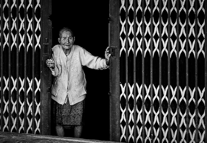 """This beautiful old lady just open the gate for me. Near Can Tho, the hub of the Mekong Delta (Vietnamese: Đồng bằng Sông Cửu Long """"Nine Dragon river delta""""), also known as the Western Region (Vietnamese: Miền Tây or the South-western region (Vietnamese: Tây Nam Bộ) is the region in southwestern Vietnam where the Mekong River approaches and empties into the sea through a network of distributaries. The Mekong delta region encompasses a large portion of southwestern Vietnam of 39,000 square kilometres (15,000sqmi). The size of the area covered by water depends on the season.<br /> The Mekong Delta has been dubbed as a """"biological treasure trove"""". Over 1,000 animal species were recorded between 1997 and 2007 and new species of plants, fish, lizards, and mammals has been discovered in previously unexplored areas, including the Laotian rock rat, thought to be extinct."""