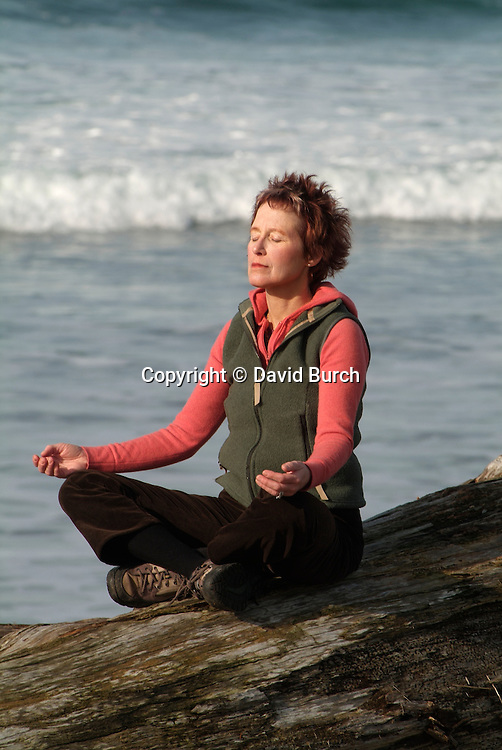 Woman sitting in yoga pose near ocean