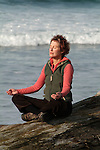 Woman sitting in yoga pose near ocean