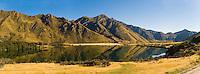 Panoramic Landscape Photo of Early Morning Reflections at Lake Moke DOC Campsite, Queenstown, South Island, New Zealand. Lake Moke, 10km from Queenstown is both a stunning lake and a department of conservation campsite (DOC campsite) with access for both caravans and campervans. In the early mornings Lake Moke is often perfectly still providing picture perfect reflections of the surrounding hills and mountains in the water. The combination of a fabulous golden hour as the sun rose over the hills, the morning mist lifting from the lake, and the rich, orange, autumn trees made this nights camping at the Lake Moke department of conservation campsite (DOC campsite) particularly special.
