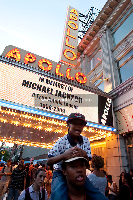 People celebrate the memory of singer Michael Jackson in front of the Apollo Theater on 125th street in Harlem, New York, USA, hours after the artist's death in Los Angeles, 25 June 2009.