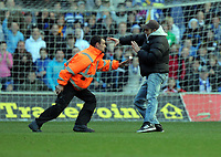 ATTENTION SPORTS PICTURE DESK<br /> Pictured: A young man is chased by security personnel after getti ng into the pitch.<br /> Re: npower Championship, Cardiff City FC v Swansea City Football Club at the Cardiff City Stadium, south Wales. Sunday 07 November 2010