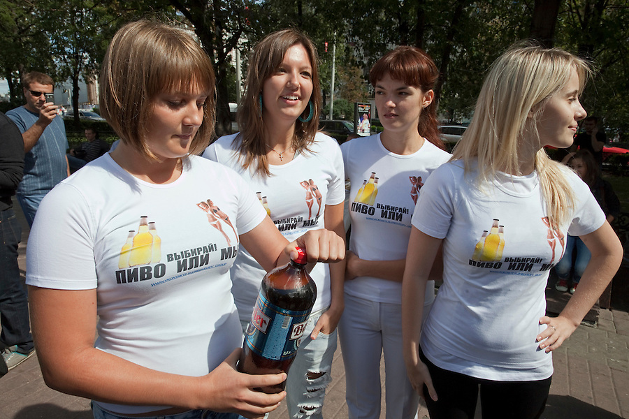 "Moscow Russia, 04/08/2011..A group of young women calling themselves the Medvedev Girls demonstrate in central Moscow in support of Russian President Dmitri Medvedev in response to similar recent actions supporting Vladimir Putin. Under the slogan ""Choose beer or us"" the women invited members of the public strolling on Pushkin Square to pour their cans of beer into buckets and as the level of donated beer rose three of the women stripped to bikinis."