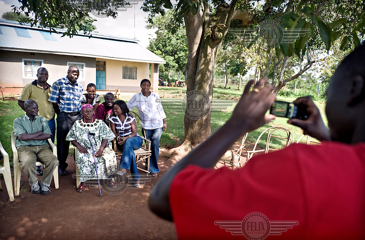 Visitors have their picture taken with Sarah Obama, Barack's step-grandmother, in the shadow of the Mango tree in front of her house. Barack Hussein Obama senior was born and raised in Kogelo village. ...