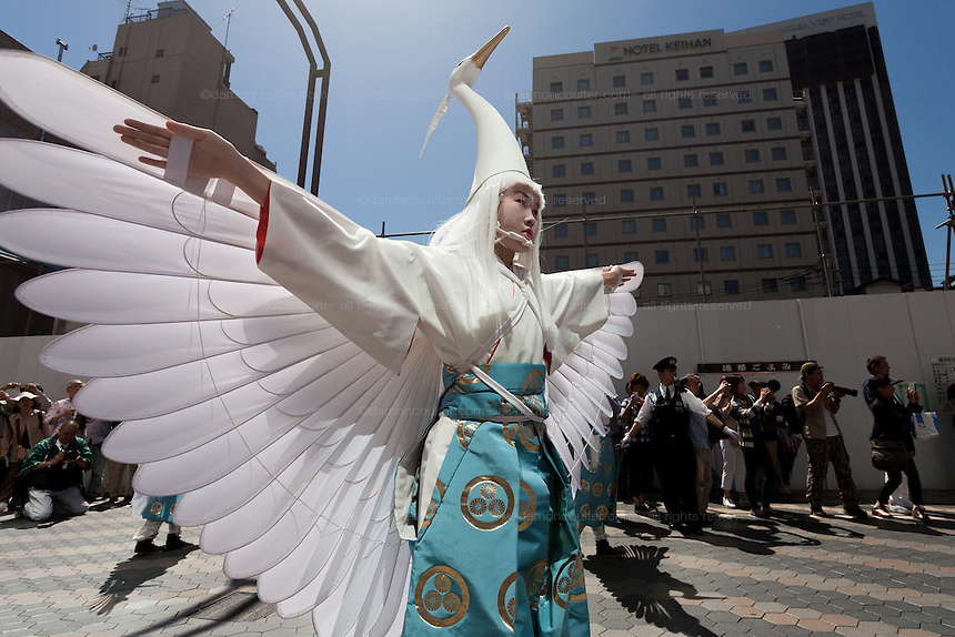 Young women dressed as herons take part in the Daigyoretsu or Grand Parade on the first day of the Sanja matsuri in Asakusa, Tokyo, Japan. Friday May 13th 2016.  The Sanja matsuri is one of the biggest festivals in Japan. Taking place over the 3 days of the second weekend of May (May 13th to 15th) it features many mikoshi, or portable shrines, that are carried around by local groups to bring blessings and prosperity to their neighbourhoods