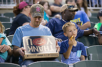 "A young fan tears into a slice of Pizza Hut pizza after winning the ""Pizza Scream"" contest between innings of the South Atlantic League game between the Kannapolis Intimidators and the Hickory Crawdads at Kannapolis Intimidators Stadium on April 22, 2017 in Kannapolis, North Carolina.  The Intimidators defeated the Crawdads 10-9 in 12 innings.  (Brian Westerholt/Four Seam Images)"