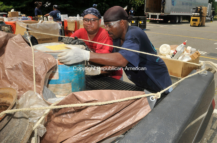 NAUGATUCK, CT-24 JULY 2010-072410IP07- Alex Gutierrez (left) and Ashante Jackson of Care Environmental Corp. remove waste products from a resident's truck during a household hazardous waste collection and medication disposal at Naugatuck High School on Saturday. Care Environmental Corp. is an outside contractor that collects, packages and disposes of the waste. Collected materials include pesticides, corrosives, flammables and medicines.<br /> Irena Pastorello Republican-American
