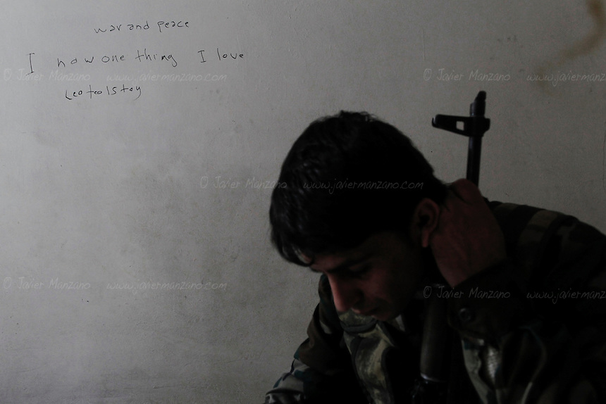 Abu Dara, a Kurdish Free Syria Army soldier belonging to the Liwa Salahadeen takes a moment to rest at his base in the besieged neighborhood of Karmel Jabl. A quote from Leo Tolstoy, written by Abu Dara describes the feeling of many of the soldiers in this city, as the battle for control of Aleppo enters it's 5th month. Abu Dara was a music student in Aleppo before the war erupted in this commercial city. Aleppo 12/06/2012..©Javier Manzano