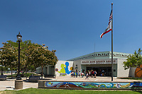 A group of children congregate outside of the South Gate Sports Center underneath a waving flag.  The sports-themed tile mosaics, flowering trees, lighting, and painted monochromatic silhouettes of athletes are all visible.