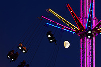 The moon is seen through a ride of the festive Winter Wonderland in Swansea, Wales, UK. Sunday 18 November 2018
