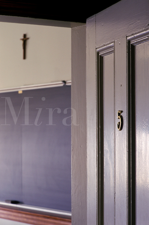 View into a classroom with blackboard and crucifix