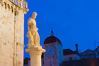 Photo of St Lawrence statue outside the Cathedral of St Lawrence at night, Trogir, Dalmatian Coast, Croatia, Europe. This photo shows the Statue of St Lawrence outside the most famous cathedral in the old city of Trogir, the Cathedral of St Lawrence in St Lawrence's Square at night. Trogir is a beautiful old town on the Dalmatian Coast of Croatia and is on the UNESCO World Heritage List thanks to it's stunning Romanesque Cathedral's and architecture. The cobbled streets of the Historic City of Trogir are littered with beautiful buildings and towering spires, places to visit and things to do. After visiting the Cathedral of St Lawrence, St Lawrence Square and Kamerlengo Fortress, there is always the option of a relaxing coffee on teh waterfront next to the bright blue Adriatic Sea of the Dalmation Coast of Croatia.