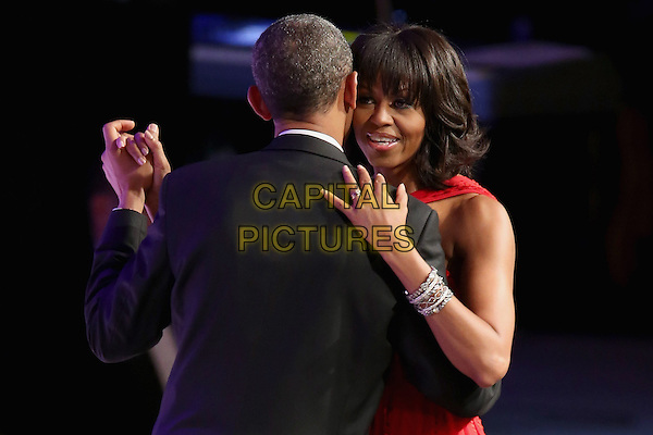Barack Obama & Michelle Obama .2013 Inauguration Ball, Washinton D.C., USA..January 21st, 2013.half length black suit tuxedo red dress back behind rear married husband wife dance dancing arm around waist profile bracelets  .CAP/ADM/CNP/CS.©Chip Somodevilla/CNP/AdMedia/Capital Pictures
