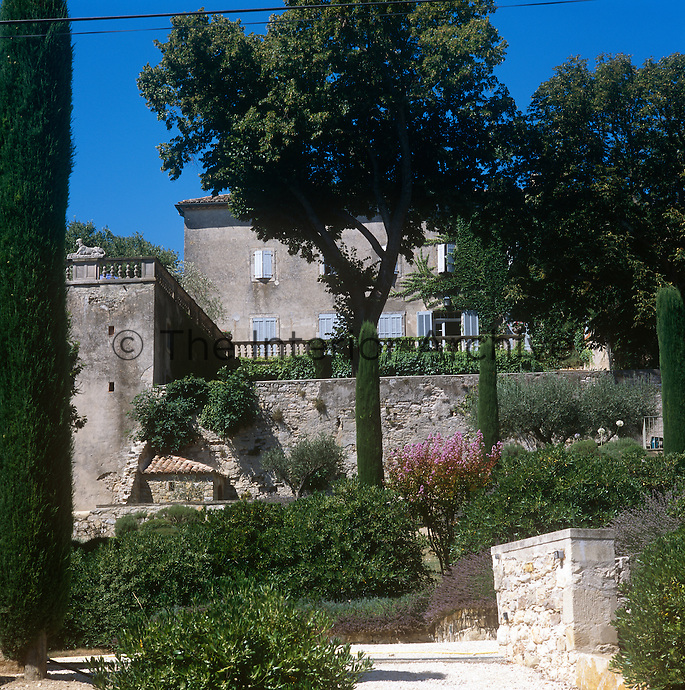 The exterior of a French chateau with a terrace looking out over the garden.