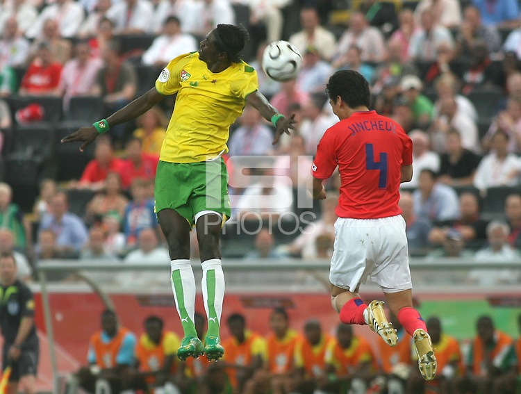 Togo's Emmanuel Adebayor (left) and Korea Republic's Jin Cheul Choi (4) go up for a header. Korea Republic defeated Togo 2-1 in their FIFA World Cup Group G match at the FIFA World Cup Stadium, Frankfurt, Germany, June 13, 2006.