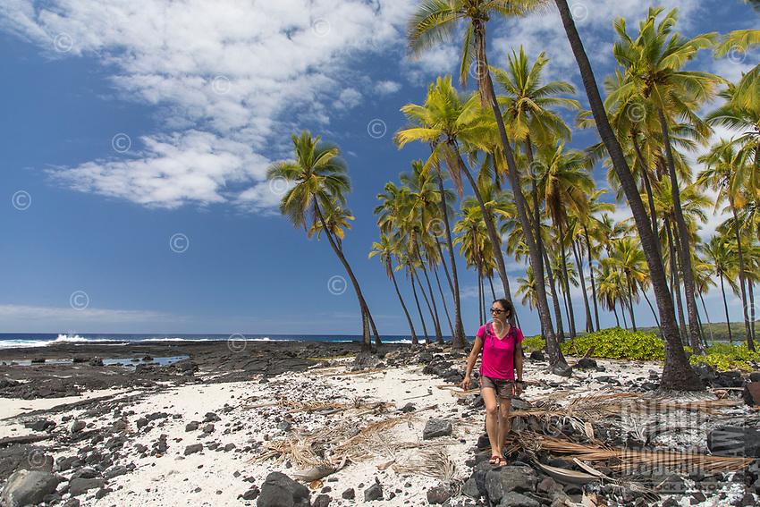 A visitor walks on the beach and rocks at Pu'uhonua o Honaunau in Kona, Hawai'i Island.