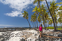 A visitor walks on the beach and rocks at Pu'uhonua o Honaunau in Kona, Hawai'i Island.