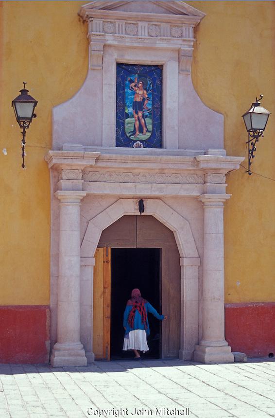 Elderly woman entering the church in the village of San Sebastian Bernal, Queretaro state, Mexico