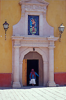 Elderly woman entering the church in the village of San Sebastian Bernal, Queretaro state, Mexico