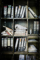 Files on shelves in abandoned Belgian powerplant http://www.vivecakohphotography.co.uk/2011/10/11/books-from-boxes/